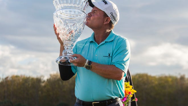 Chubb Classic champion Joe Durant kisses his trophy on the final day of the Chubb Classic in Naples on Sunday, Feb. 18, 2018.