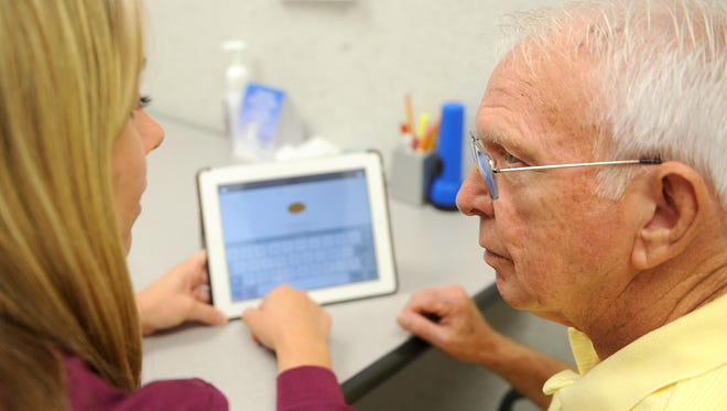 John Cornell sits with his speech therapist, Allison Swain, to continue therapy with the help of an iPad application. Cornell is in the early stages of Alzheimer's, and the application should allow him to communicate in the later stages of the disease.