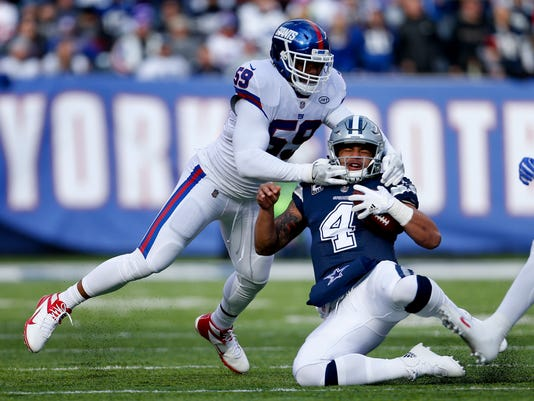 CORRECTS TO COWBOYS QUARTERBACK DAK PRESCOTT NOT ZAC DYSERT - Dallas Cowboys quarterback Dak Prescott (4) slides as he takes a hit from New York Giants outside linebacker Devon Kennard (59) during the first quarter of an NFL football game, Sunday, Dec. 10, 2017, in East Rutherford, N.J. (AP Photo/Adam Hunger)