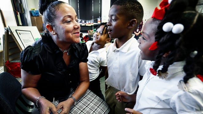 Downtown Elementary School principal Debra Martin (left) reads about butterflies with kindergarten students (left to right) Taylor Cox, 5, Romerick Humphrey, 5, and Jarvia Morgan, 5, during class Thursday afternoon. Martin, a former Master Sergeant, served 20-years in the U.S. Army.