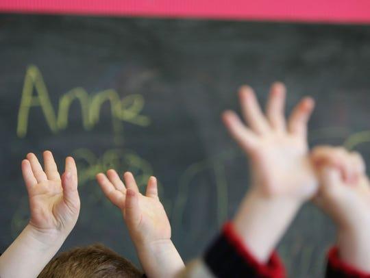 Children wave their hands.