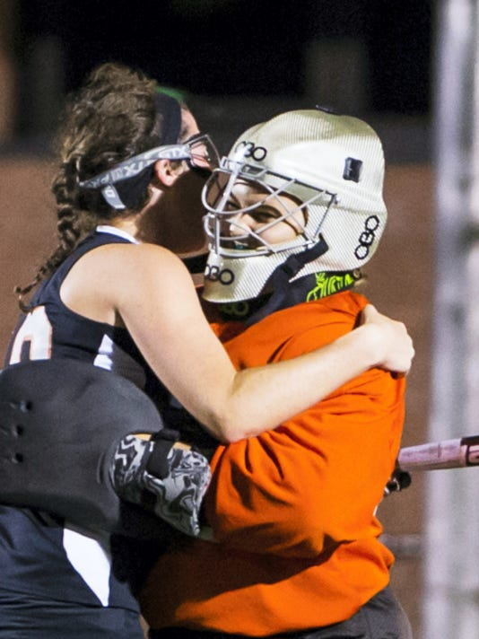 Palmyra's Cheyenne Sprecher gets a hug from teammate Carli Herman after she blocked the first of two penalty strokes by Lower Dauphin's Rachel Yeager during overtime on Tuesday. Yeager converted the second stroke try, though, to give LD a 3-2 win.