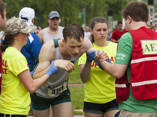 Terence Hughes, from Hanover, New Hampshire, is helped by the medical staff after collapsing at the finish line during the People's United Bank Vermont City Marathon in 2016.