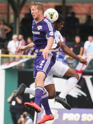 Louisville City forward Bryan Burke goes up for a header against Montreal's Mitchel Bringolf Wednesday night. Aug. 5, 2015