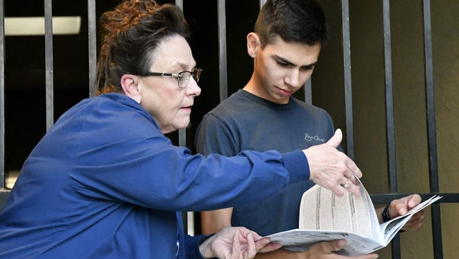 Donna Ballard helps Jeremy Torres find an item in his voter information guide while in line at the Sierra Baptist Church on Tuesday, November 6, 2018.