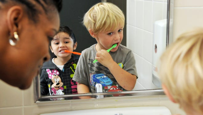 Nursing supervisor Travia Williams watches 3-year-olds Luna Castillo and Justice Lindsey brush their teeth in front of a bathroom mirror in the Head Start classroom at Cocoa High School in Brevard County, Fla.