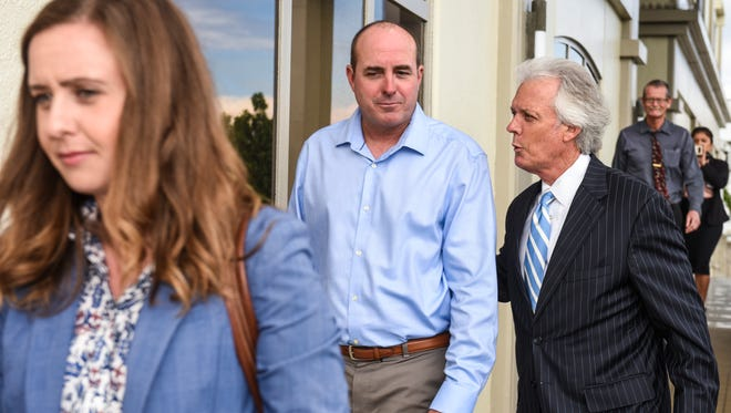 Hansen Helicopter Inc. owner John D. Walker, in light blue shirt, leaves the District Court of Guam with his lawyers, Mack Martin, right, and Amber Martin, after a 2018 hearing. A judge on Friday ordered Hansen Helicopter Inc. to turn over documents sought in a grand jury subpoena.  PDN file photo.