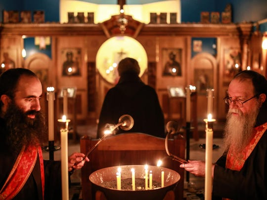 Father Ambrose (left) and Father Basil light candles during vespers on Monday November 16, 2015 in the sanctuary of the Holy Transfiguration Skete monastery in Eagle Harbor located in Michigan's Upper Peninsula.