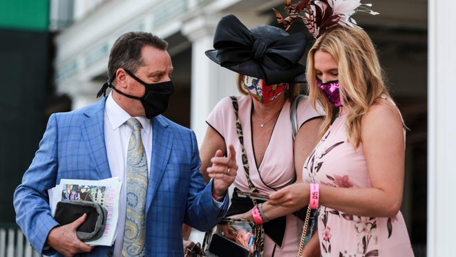 The first few patrons arrived for the Kentucky Oaks with masks on Friday morning at Churchill Downs. Large protests are expected Saturday outside the track after Black residents asked that the event be canceled amid racial unrest.