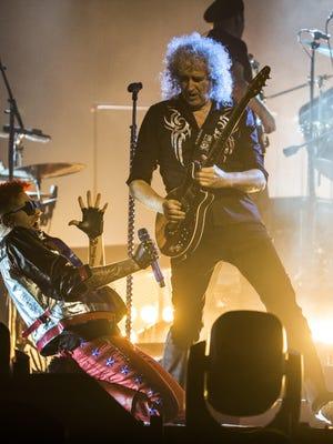 Adam Lambert kneels beneath Queen lead guitarist Brian May as they perform during the Queen + Adam Lambert concert at Gila River Arena in Glendale, Ariz. on June 23, 2017.
