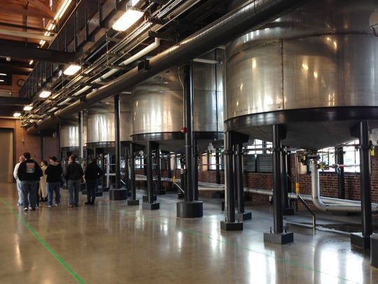 Stainless steel fermenters tower above visitors at the Angel's Envy distillery in Downtown Louisville. Corn, rye and malted barley are ground, fermented into a type of beer and then distilled to create clear whiskey. The liquid is aged in new charred oak barrels for years, giving the bourbon both its brown color and rich taste.
