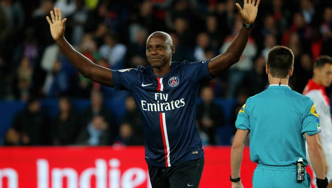 Carl Lewis gestures prior to the start of the League One soccer match between Monaco and Paris Saint Germain, at the Parc des Princes stadium, in Paris, France, Sunday, Oct. 5, 2014.