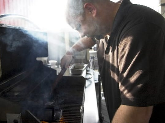 Brickyard Tavern owner and cook Scott Hamberger grills on the patio a few months ago.