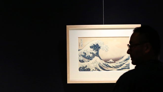 """In this Nov. 18, 2016 photo, a visitor photographs """"The Great Wave off Kanagawa,"""" Katsushika Hokusai's most well-known work, in the series 36 Views of Mount Fuji during a press preview of the Sumida Hokusai Museum in Tokyo's Sumida Ward. The museum dedicated to Japanese woodblock print artist Katsushika Hokusai, creator of some of the most iconic art of the genre, opened Tuesday, Nov. 22, 206 in the neighborhood he lived in some two centuries ago."""