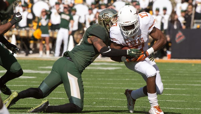 Texas wide receiver Ryan Newsome, right, is tackled by Baylor safety Chance Waz on Dec. 5, 2015.