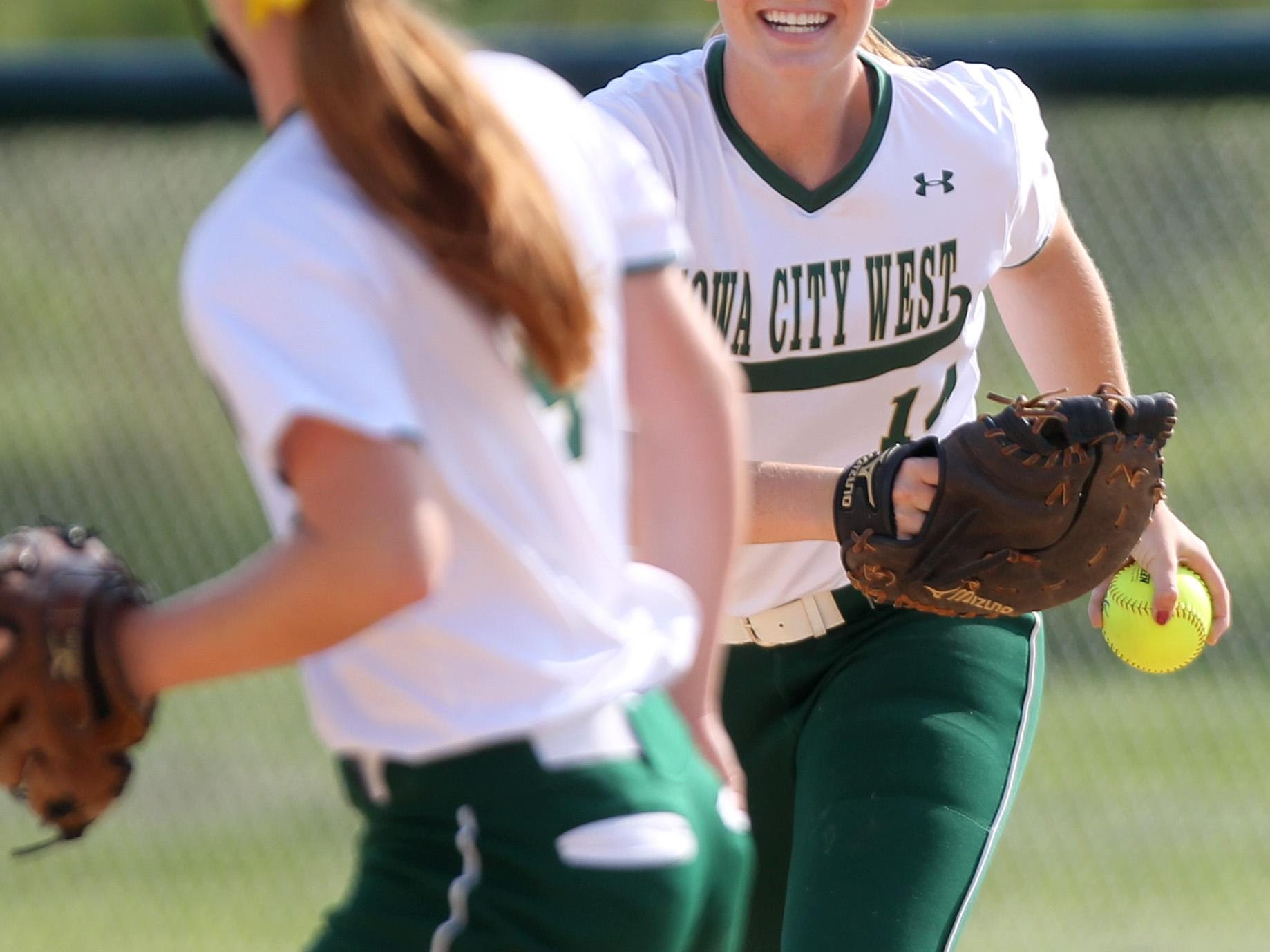 West High's Laynie Whitehead runs up to congratulate pitcher Jessie Harder on a strikeout during the Women of Troy's game against Linn-Mar on Thursday, July 9, 2015. David Scrivner / Iowa City Press-Citizen