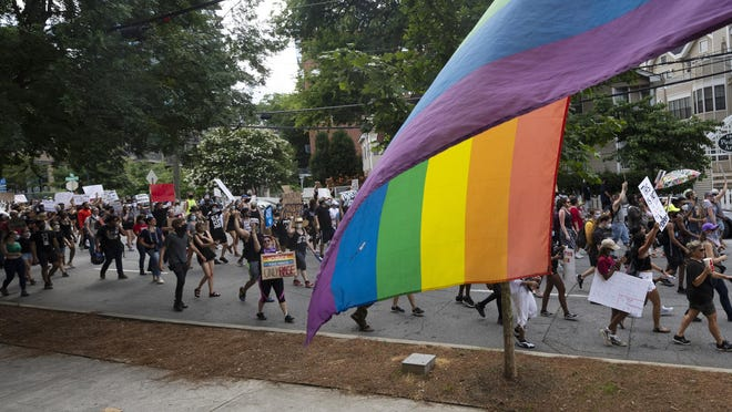 "Demonstrators pass a gay pride flag as they walk up Piedmont Avenue during a protest billed as ""Justice for Tony McDade'"" begun at Piedmont Park on Sunday in Atlanta."