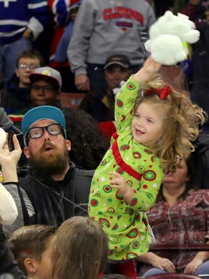 Olivia Van Patton throws a stuffed animal onto the ice during the Greenville Swamp Rabbits' game against the South Carolina Stingrays at the Bon Secours Wellness Arena on Friday night, December 2, 2016. The stuffed animals will be given to Toys for Tots.