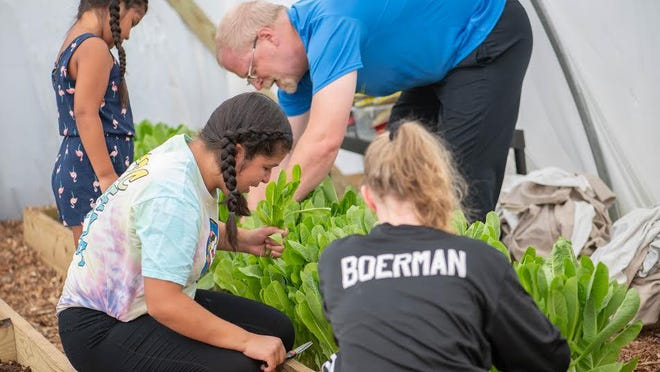 Holland teacher Bill Boerman (in blue) tending to the Holland Middle School greenhouse with students.