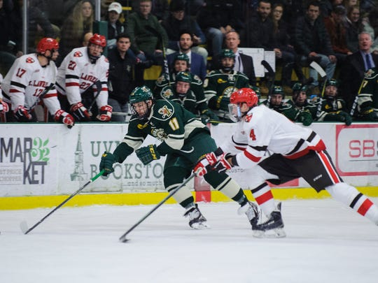 Vermont forward Conor O'Neil (11) skates down the ice