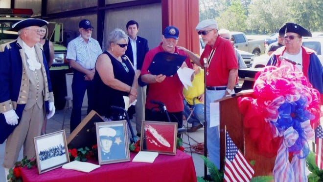 Jim Cox, second from right, greets Luther and Sharon Donald after the Moselle Neighborhood Watch couple accepted a certificate of patriotism for the group during the unveiling of a plaque to honor Medal of Honor recipient Roy Wheat  at the new Moselle Fire Department. At right is Ed Holland and at left is Royce Stringer, both members of the Jacob Horger Chapter of the Sons of the American Revolution.