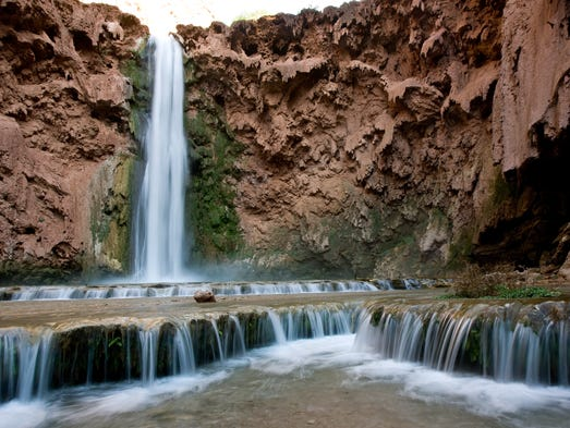 Water flows from Mooney Falls, one of the the Havasupai