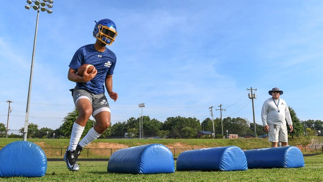 Wren High School football quarterback Tyrell Jackson runs in a drill near coach Jeff Tate during practice in July.