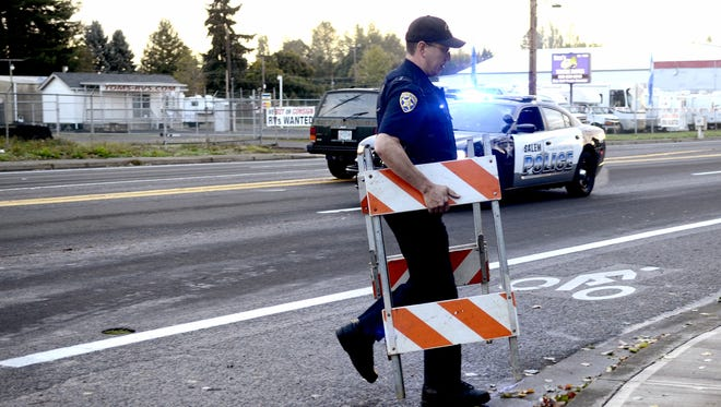 A Salem police officer removes barricades on State Street and 37th Ave. SE following an officer-involved auto accident at State Street and Lancaster Road in Salem on Monday, Oct. 27, 2014.