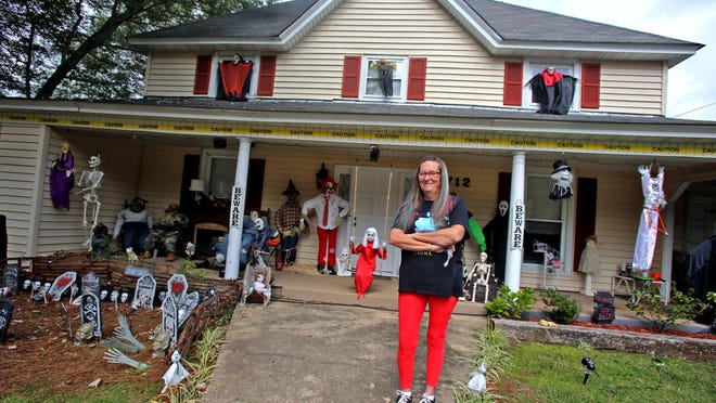 Sheri Hauck stands in front of her decorated house on Warren Street in Shelby on Friday.