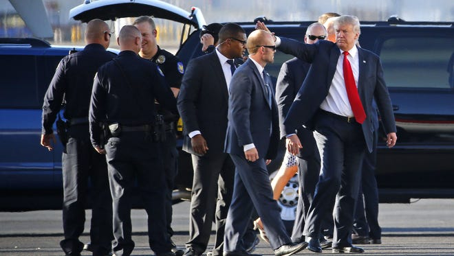 Donald Trump thanks Phoenix police officers as he prepares to board his plane at Phoenix Sky Harbor International Airport on June 18, 2016.