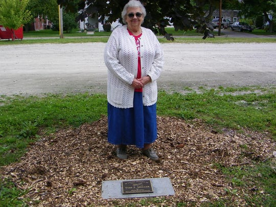 Betty Marlow Miller stands next to the plaque that