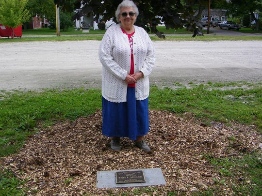 """Betty Marlow Miller stands next to the plaque that was installed under a red maple tree near the Elmore Historical Society Barn in honor of her late husband, Tom Miller. Betty's son and Tom's stepson, Barry Marlow – who referred to Tom as his """"bonus dad"""" – was the impetus behind the plaque."""