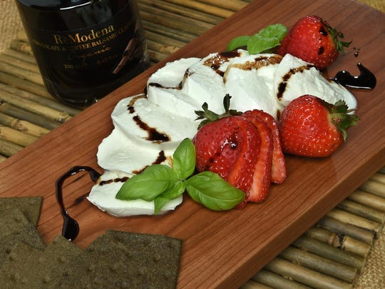 """Instead of a mix of cheeses, a party platter can feature a single """"big"""" cheese, like this fresh buffalo mozzarella from Italy presented with basil, strawberries, and drizzles of sweet, rich, coffee-chocolate balsamic vinegar."""