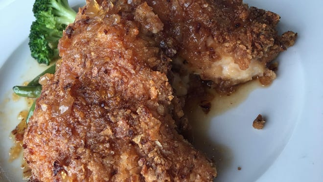 Onion-crusted chicken at Yellow Dog Cafe is legendary and addictive: a fat, boneless breast of chicken coated with crispy onions, given a citrusy-sweet glaze, but not too much, over mashed potatoes and green beans.