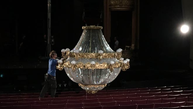 """A stage hand works on the iconic two-ton """"Phantom of the Opera"""" chandelier on display Thursday."""