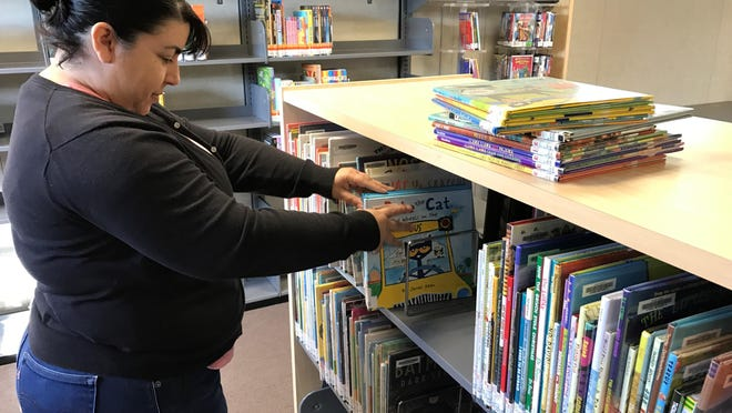 Faythe Arrendondo, a collection and technical services manager for Tulare County Library system, logs books at the London Library before its grand opening.