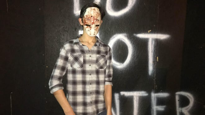 A chainsaw-wielding maniac poses after a good slashing at the Haunted Doom Saturday.