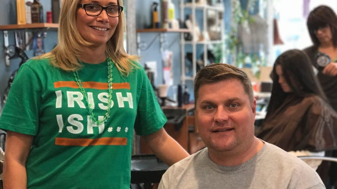 Samantha Rehe pauses shortly after cutting the hair of her client, meteorologist Dave Curren of News 12 New Jersey.