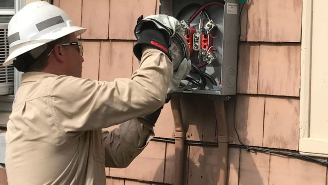 New York State Electric & Gas Corp. meter technician Steve Marshall installs the company's first smart meter at a West Jay Street house in Ithaca on July 20, 2017.