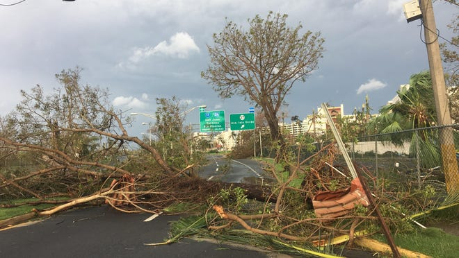 Streets around San Juan were clogged with downed trees and debris a day after Hurricane Maria tore through the island.