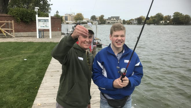 "Neenah High School student Andrew Arendt, left, shows off a fish caught with Ben Goldbeck during a ""Reel Choices"" program where fishing team members were paired with students with intellectual disabilities for a day of fishing at Riverside Park."