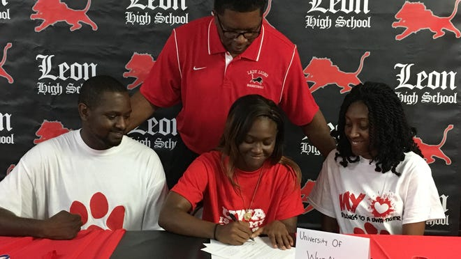 Leon High point guard Jala Williams signs Monday to play basketball at the University of West Alabama. She was joined by her parents, Rashad and Larissa Robinson (seated), and Lions coach Bruce Daniels.