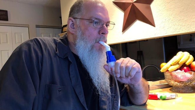 Retired coal miner John Robinson uses a nebulizer during his daily breathing treatments for black lung disease on Thursday, Jan. 24, 2019 in Coeburn, Va.