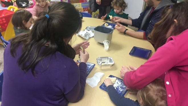Kids at Tot Shabbat braid Challah.
