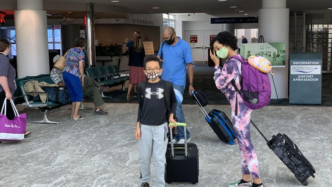 Mask-wearing airline passengers arrive at Daytona Beach International Airport on Friday, June 12, 2020.