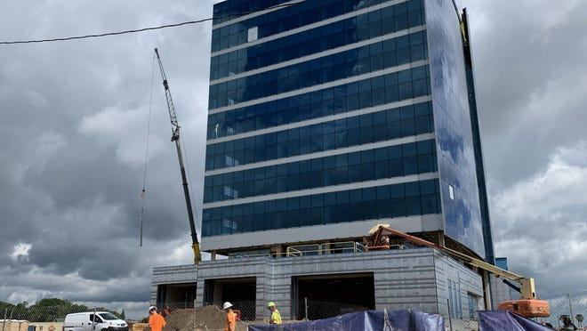 Construction workers can be seen walking in front of the future headquarters for Brown & Brown Insuraance on Wednesday, May 27, 2020. The 11-story office tower is on track to open in December, said company Chairman J. Hyatt Brown.