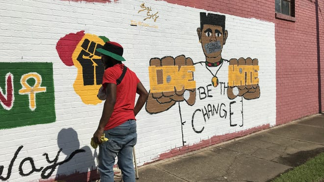 Artist Sai St. John painted a mural on the side of this cousin's store at the corner of 12th and Chestnut streets. He said he wanted to send a positive message to the city.