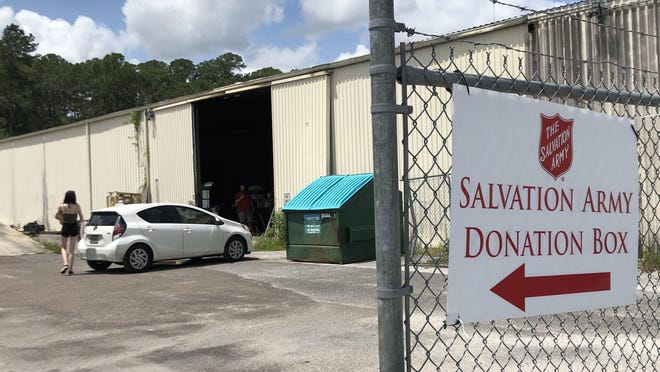 A woman drops off a donation at the Salvation Army Family Store, 55 NW 23rd St., on on Tuesday in Gainesville. The nonprofit thrift store reopened Tuesday following a temporary closure due to COVID-19. It will not accept mattress donations at this time and other items will be donated through contactless drop off.