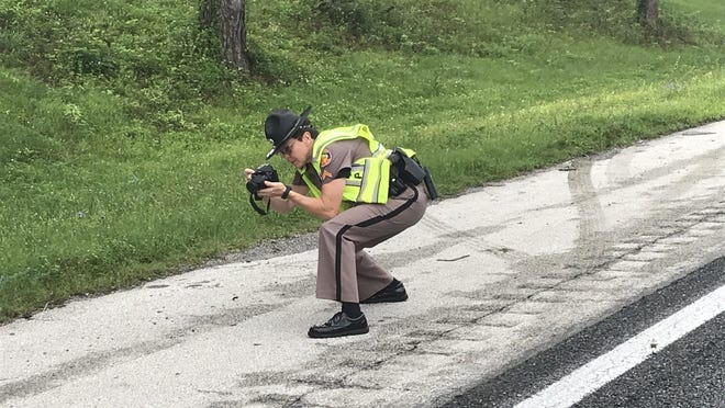 Cpl. Kristine Schultz, with the Florida Highway Patrol, takes photographs Tuesday morning along I-75 south of Ocala where the body of a man was found, the victim of an apparent hit-and-run incident overnight.
