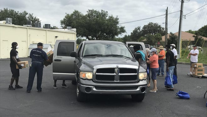 Volunteers hand out food and other provisions as vehicles drive up  the distribution point in Dunnellon on Friday morning.